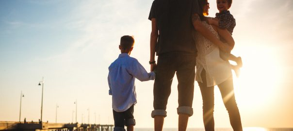 A young family stands on the sand of Venice beach California, watching the sun set into the Pacific ocean.  The stand close, hugging and holding hands.