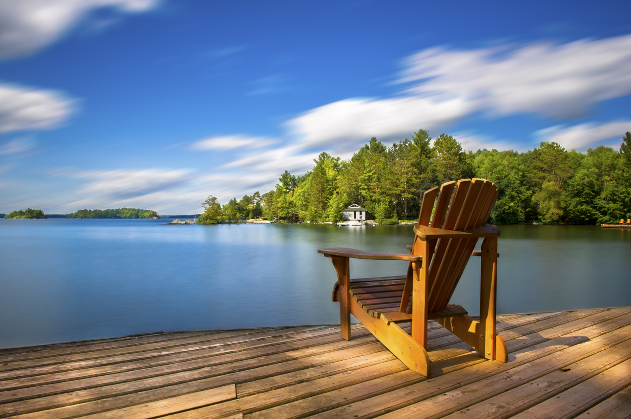 Adirondack chair on a wood dock facing a calm lake. Across the water is a white cottage nestled among green trees. There is a boat dock on the water in front of the cottage.